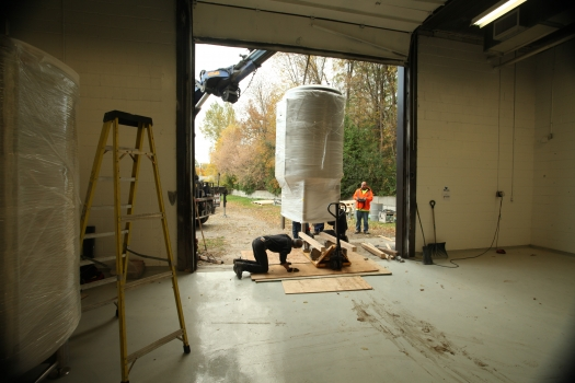 A brewery tank, wrapped in a protective covering, sits at the entrance of the brewery, waiting to be moved into place.