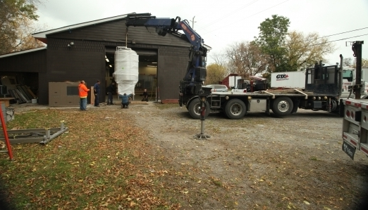 An exterior view of a brewery tank being lifted by a boom truck.
