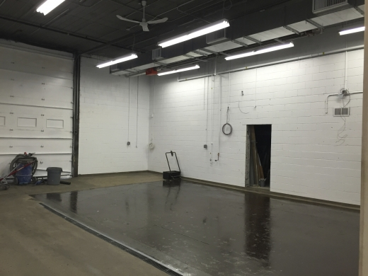 A thick layer of shiny floor epoxy covering one half of a brewery floor.