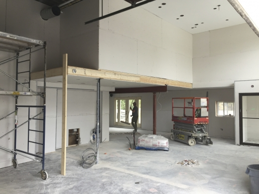 A freshly drywalled space, with scaffolding and a lift truck nearby.