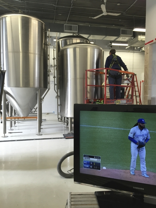 A man inspects a fermentation tank in the background, while a TV plays a Blue Jays game in the foreground.