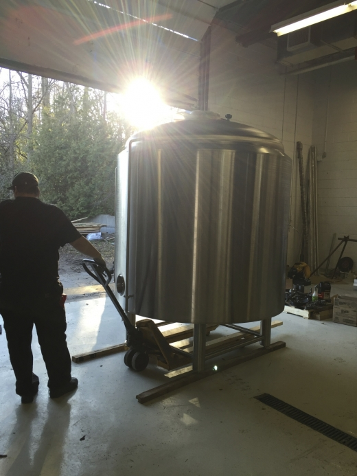 A man wheels a brewhouse vessel into the brewery.