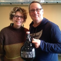 A man and woman smile and hold a growler